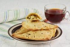 Empanadas hechas en casa del triángulo con queso y la taza de té Imágenes de archivo libres de regalías