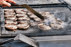 Empanadas jugosas de la carne de la hamburguesa en parrilla de cocinar caliente Foto de archivo libre de regalías