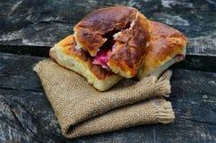 Empanadas recientemente cocidas con las bayas (frambuesas, manzanas, cerezas) en la tabla de madera Estilo del pueblo Fotografía de archivo