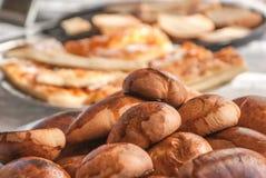 Empanadas y pizza cocidas en la tabla de cocina Foto de archivo