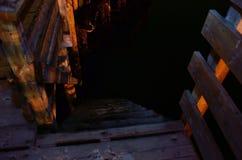 Empape la escalera de madera del embarcadero que lleva abajo al nivel del mar en la noche Imagenes de archivo