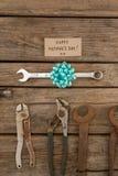 Empapele con las herramientas felices del texto y de la mano del día de padres en la tabla Foto de archivo