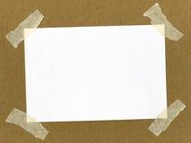 Empapele sujetado con cinta adhesiva en la cartulina Fotos de archivo