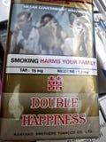 Empaquetado y etiqueta de advertencia que fuman -- Un paquete irónico del cigarrillo exhibe el doble de la marca Imagenes de archivo