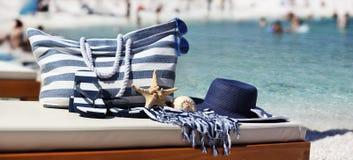 Empaquete con el sombrero, sandalias, las estrellas de mar, la cáscara del mar y la toalla en el beac Imagenes de archivo