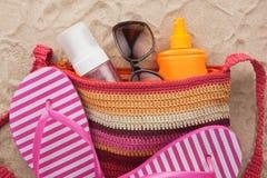 Empaquete con los accesorios de la playa que mienten en la arena de la playa Imágenes de archivo libres de regalías
