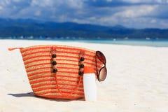 Empaquete, los vidrios de sol y suncream en la playa tropical Foto de archivo