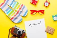 Empaquetez mes vacances, cadeaux, verres, appareil-photo, réveils et sable Image libre de droits