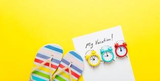 Empaquetez mes vacances, réveils et sandales Photo stock