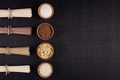 Empaquette les nouilles crues avec l'ingrédient dans des cuvettes en bois sur le fond rayé noir de tapis avec l'espace de copie,  Photo stock