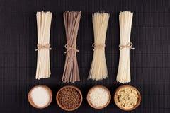 Empaquette les nouilles crues avec l'ingrédient dans des cuvettes en bois sur le fond rayé noir de tapis avec l'espace de copie,  Photos stock