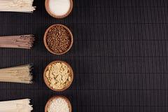 Empaquette les nouilles crues avec l'ingrédient dans des cuvettes en bois sur le fond rayé noir de tapis avec l'espace de copie,  Photographie stock