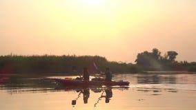 Emparéjese de gente en flotadores de los kajaks en un río tranquilo en una puesta del sol metrajes