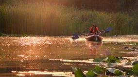 Emparéjese de gente en flotadores de los kajaks en un río en una puesta del sol Cámara lenta metrajes