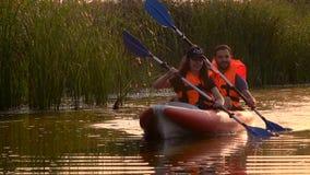 Emparéjese de gente en flotadores de los kajaks en un río en una puesta del sol Cámara lenta almacen de video