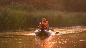 Emparéjese de gente en flotadores de los kajaks en un río en una puesta del sol Cámara lenta almacen de metraje de vídeo