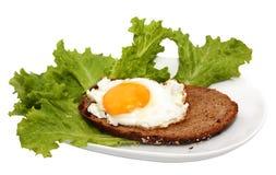 Emparedado con un huevo frito en una placa blanca Imagen de archivo libre de regalías