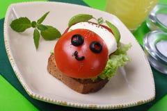 Emparedado divertido con queso y el tomate de la mozarela Foto de archivo libre de regalías