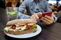 Emparedado en una placa La mujer va a comer el almuerzo y está utilizando el teléfono en café Fotos de archivo libres de regalías