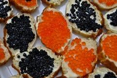 Emparedados con el caviar rojo y negro Imagenes de archivo