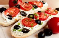 Emparedados con los tomates, las aceitunas y el queso Feta Imágenes de archivo libres de regalías