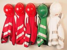 Emparede la suspensión con el chaleco y los cascos para un equipo del encargado de la emergencia fotos de archivo libres de regalías