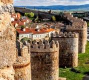 Emparede los ladrillos de piedra amarillos hechos España de Ávila del bastión de la torre con la vista de la ciudad y del campo Foto de archivo libre de regalías