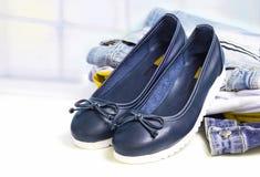 Empareje los zapatos planos del estilo femenino del deporte en fondo de la ropa de los vaqueros Foto de archivo libre de regalías