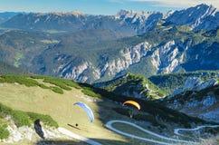 Emparelhe os paraplanes que lançam-se e que sobem em montanhas bávaras dos cumes Fotografia de Stock