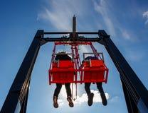 Emparelhe ter o divertimento no balanço em uma construção alta contra o céu azul Fotografia de Stock