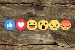Empathetic Emoji Reactions on wooden background. Kiev, Ukraine - February 07, 2017: Facebook like button 6 Empathetic Emoji Reactions printed on paper and placed Stock Photography