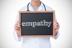Empathy against doctor showing little blackboard Stock Photography