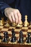 Empeño móvil de la mano en tarjeta de ajedrez Foto de archivo libre de regalías