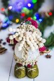 Empequeñezca, un juguete en una tabla de madera blanca en guirnalda del ` s de la Navidad verde del fondo y del Año Nuevo de luce Imágenes de archivo libres de regalías