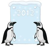 Emperor penguins with poster 2012 Royalty Free Stock Photos