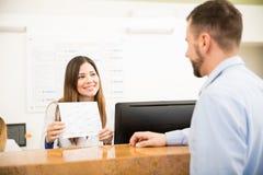 Empfangsdame, die Dienstleistungen und Kosten zeigt stockbilder
