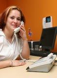 Empfangsdame, die Telefon ihrer Firma beantwortet lizenzfreie stockbilder