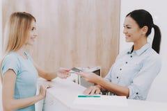 Empfangsdamen-Gives Customer Business-Karte im Salon stockfoto