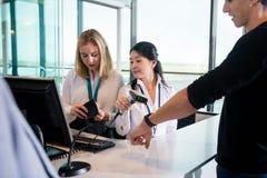 Empfangsdamen-Scanning Passengers Smart-Uhr während Kollege Che Stockfotografie