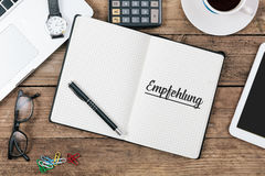 Empfehlung, German text for Referrals in notebook on office desk Stock Images