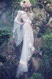 Empfindliche blonde Nymphe gekleidet im hellen Kleid Stockfoto