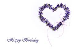 Empfindliche Frühlingsveilchen in Form eines Herzens auf einem weißen Hintergrund Alles Gute zum Geburtstag Stockbild