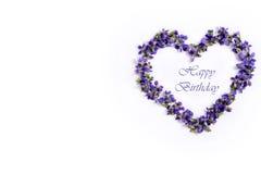 Empfindliche Frühlingsveilchen in Form eines Herzens auf einem weißen Hintergrund Alles Gute zum Geburtstag Stockfotos