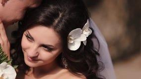Empfindliche Nahaufnahme schoss von den umarmenden Jungvermähltenpaaren Die schöne reizend Braut mit natürlichem Make-up und dem  stock footage