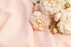Empfindliche sahnige Rosen auf einem Spitzegewebehintergrund Stockbild