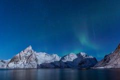 Empfindliche, weiche Nordlichter über schneebedeckten Bergen im Mondschein Lizenzfreies Stockbild