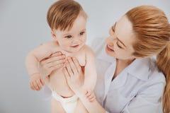 Empfindlicher ausgezeichneter Kinderarzt, der ihre kleine Patientenfirma genießt Stockbilder