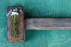 Empfindlicher Blumenstrauß von Blumen bedeckt den schweren rauen Hammer anschlag Stockfotos