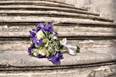 Empfindlicher Brautblumenstrauß auf den grauen Steinschritten Stockfotos