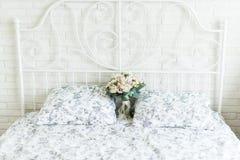Empfindlicher Brautblumenstrauß auf einem Brautbett Stockfotografie